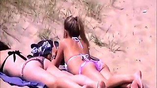 Two sexy babes in tight bikinis enjoy the sun on the beach