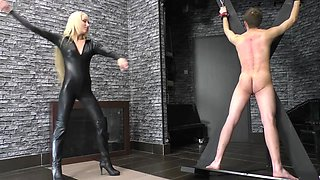 Hot young black leather sadistic dominatrix whips her slave tied to the cross