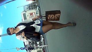 Hidden camera follows a brunette with great legs and short