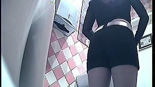Hot brunette young chick in black panties pisses in the toilet