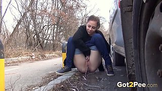 Kinky amateur chick hides behind the car and pisses outdoors right away