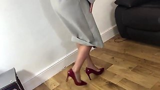 She dangles her sexy red heels wearing a coat